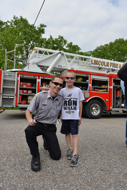 LF&R Fire Captain with a child in front of a fire truck at the zoo fun run event.