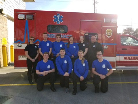 The group of fire explorers posing in front of an ambulance
