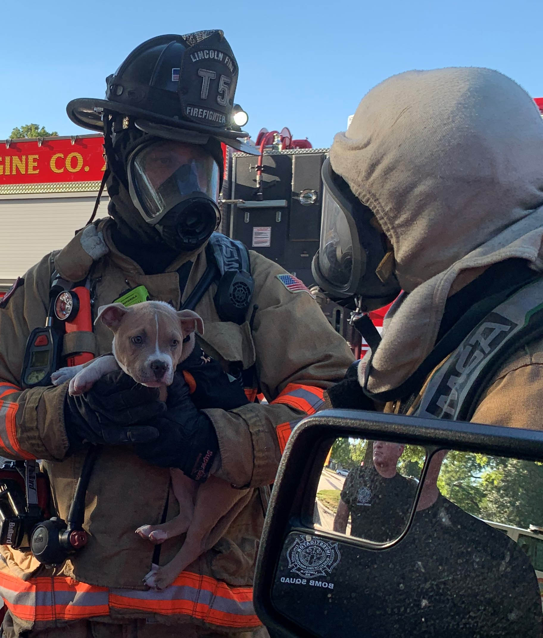 Firefighter from truck 5 holding a puppy who was just rescued from a fire