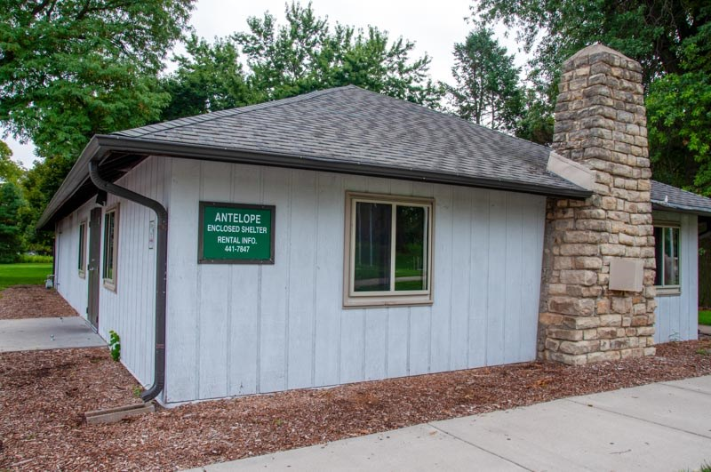 A profile shot of Antelope Enclosed shelter looking at a wall with a chimney and a Green Sign with text that reads: Antelope Enclosed Shelter Rental Info. 441-7847.