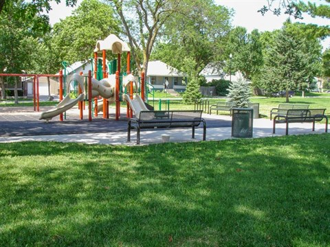 The playground at the American Legion Park has slides, swings, and a rubber play surface. There are large shade trees and benches lining the area provide space to rest and enjoy the space.